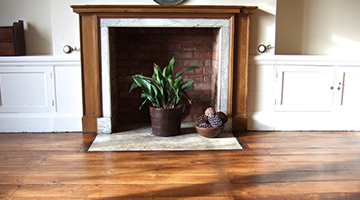 Old elm floor restored in a dining room with fireplace.